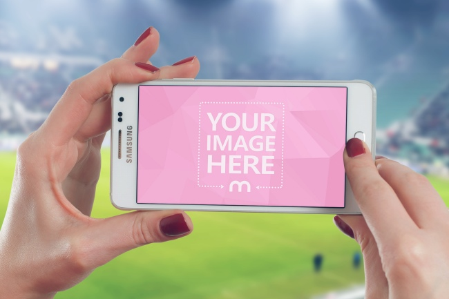 Woman Holding Smartphone at Sports Event Mockup preview image