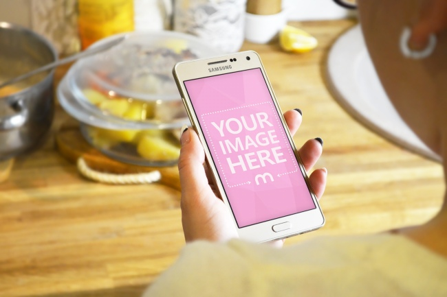 Woman Looking at Smartphone in Kitchen preview image