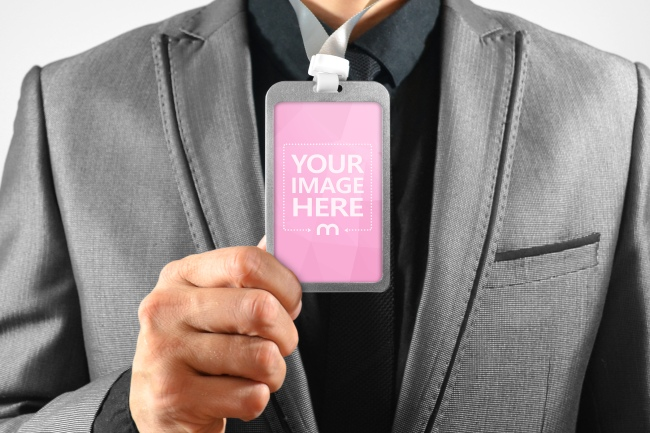 Man in Suit Holding Lanyard Name Tag in Portrait View Mockup preview image