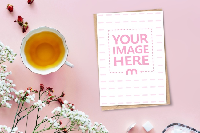 Postcard on Pink Surface with Flowers Mockup Generator preview image