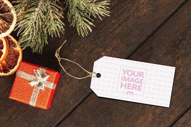 Christmas Present Label on Wood Desk Mockup preview image