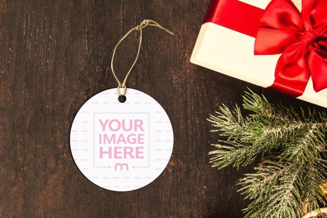 Round Christmas Present Label Tag on Wood Desk Mockup