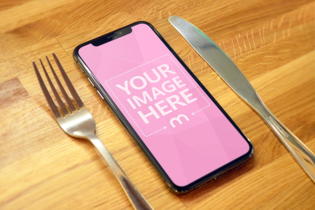 iPhone Xs on Wood Table Next to Fork and Knife Mockup preview image