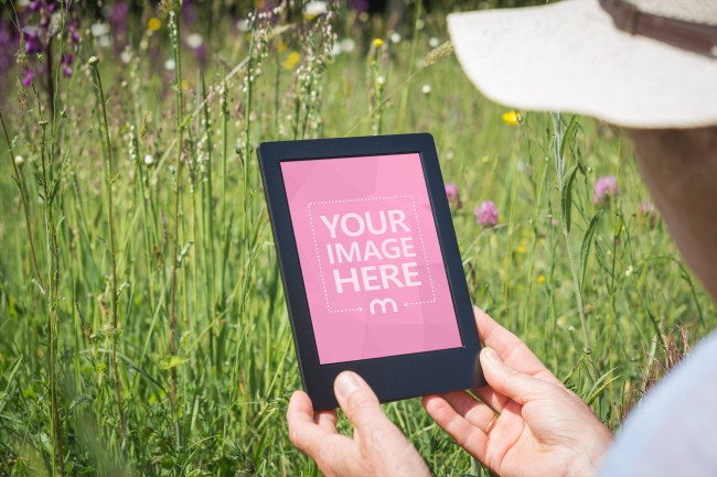 Woman Reading E-Book Outdoors Mockup Generator preview image