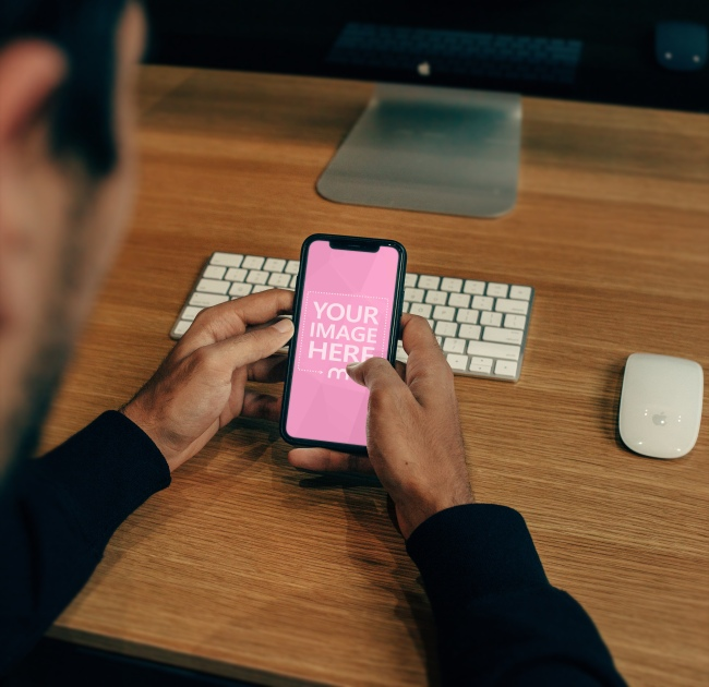 Man Typing on iPhone X Mockup Generator preview image