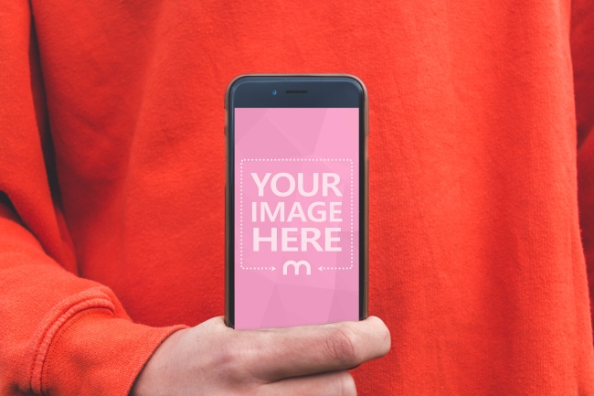 Man in Red Sweater Presenting iPhone Screen Mockup Generator preview image