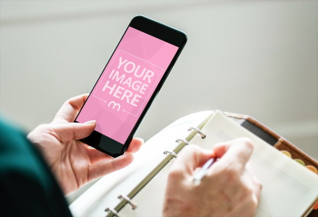 Woman Holding iPhone and Taking Notes Mockup Generator preview image