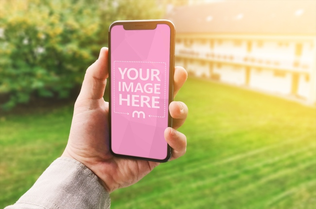 Holding iPhone X in Hand on Sunset Garden Background Mockup Generator preview image