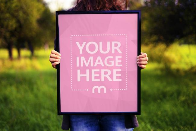 Woman Holding Photo Frame Outdoors Mockup Generator