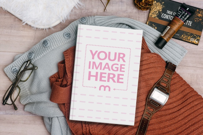 Book Lying on the Floor on Top of Clothes Mockup Generator preview image