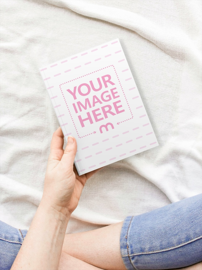Woman Holding a Book in Hand and Sitting on a Bed Mockup preview image
