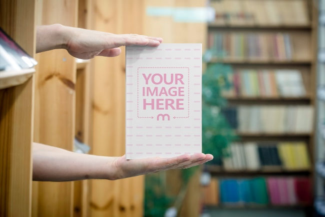 Man Showcasing Book on Library Background Mockup preview image