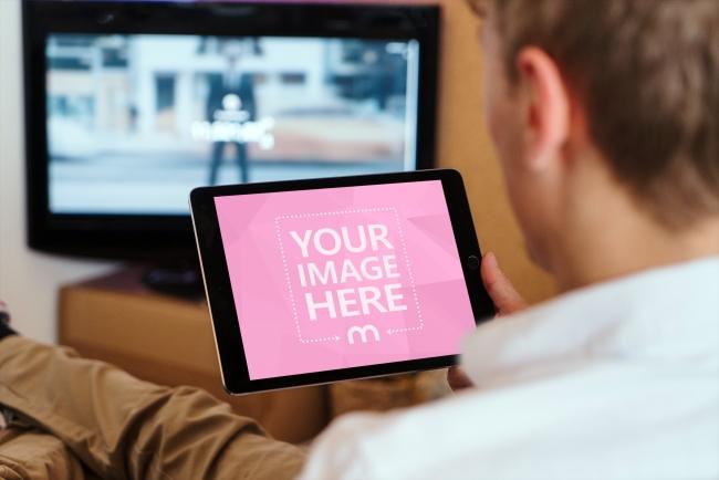 Man Looking at iPad Screen Mockup