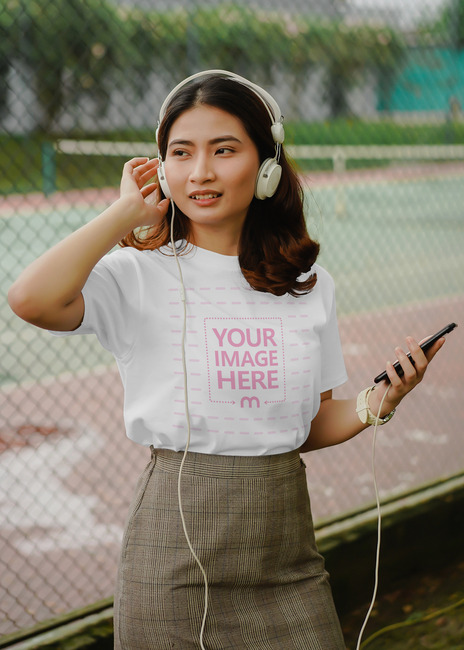 T-Shirt Mockup Featuring a Smiling Woman Wearing Headphone preview image