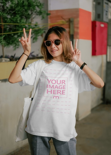 T-Shirt Mockup Featuring Model Doing Peace Sign preview image