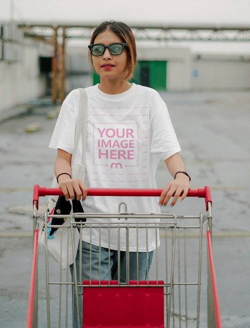 T-Shirt Mockup With a Young Woman Holding a Shopping Cart