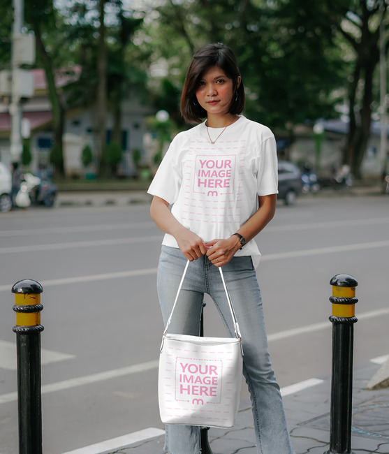 T-Shirt Mockup of a Woman Holding Her Bag on the Sidewalk preview image