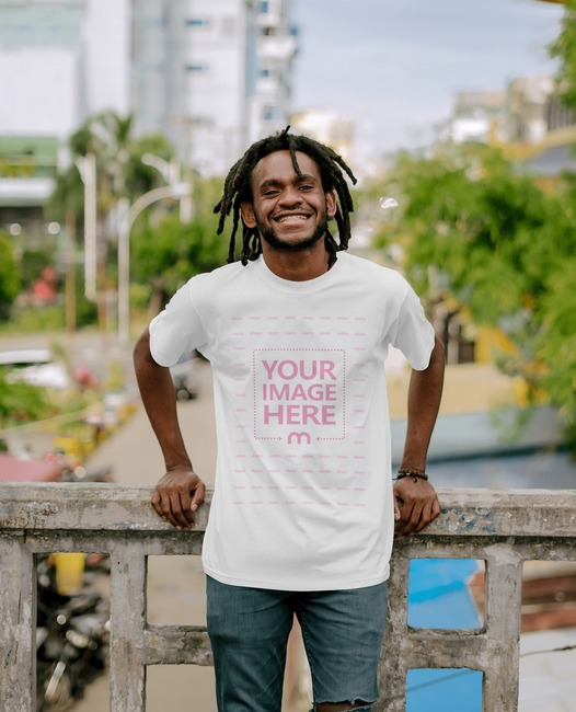 T-Shirt Mockup With Smiling Black Man Leaning to a Stone Fence preview image