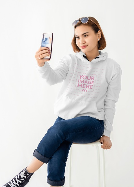 Hoodie Mockup With a Sitting Young Woman Taking Selfie