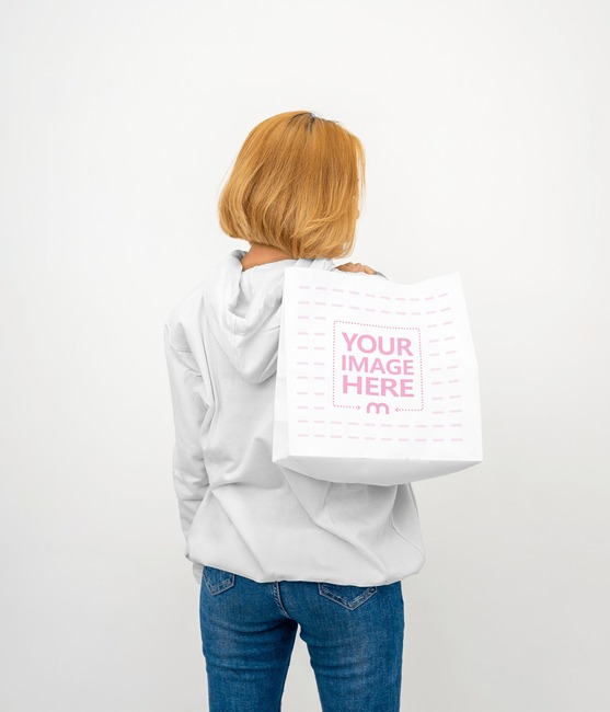 Paper Bag Mockup With a Woman Wearing Her Oversized Hoodie