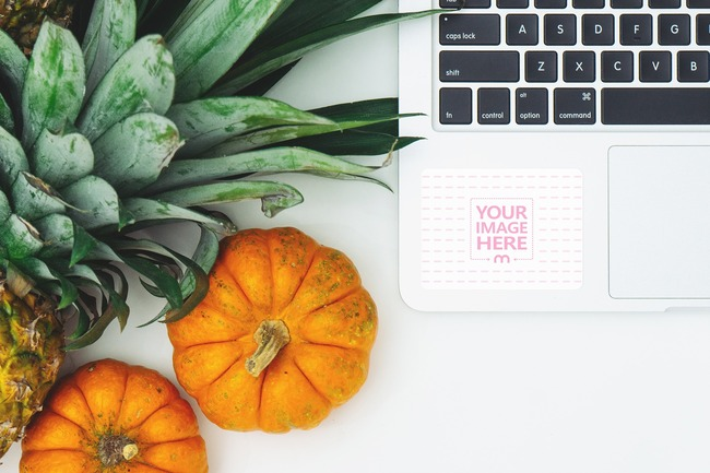 Laptop Sticker Mockup Next to Pumpkins and Pineapple