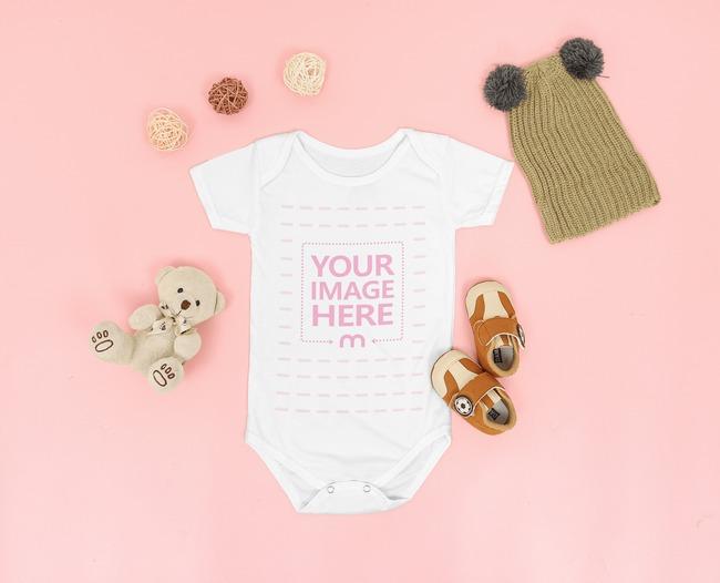 Flatlay Baby Bodysuit Mockup With a Small Teddy Bear