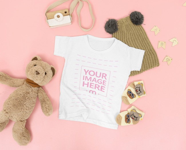 Mockup of a Baby Shirt Flat Laid Over Pink Background