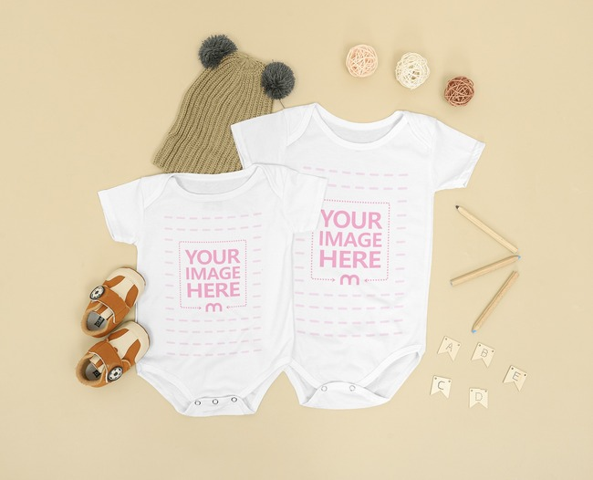 Two Size Baby Onesie Mockup Laid Over a Brown Background