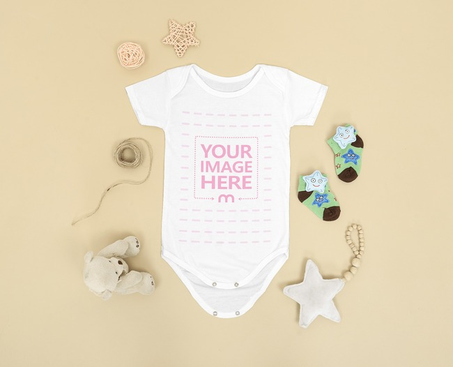 Mockup of a Baby Bodysuit Surrounded by Some Baby Accessories