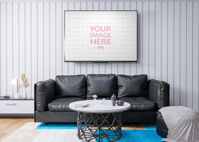 Mockup of a TV on top of a Black Sofa in a Room