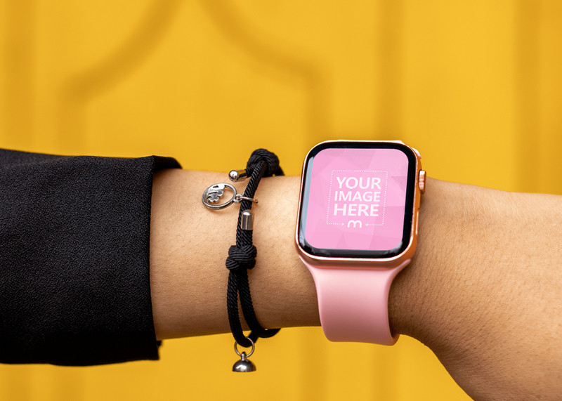 Pink Smartwatch Mockup Put on a Woman Hand on Yellow Background preview image