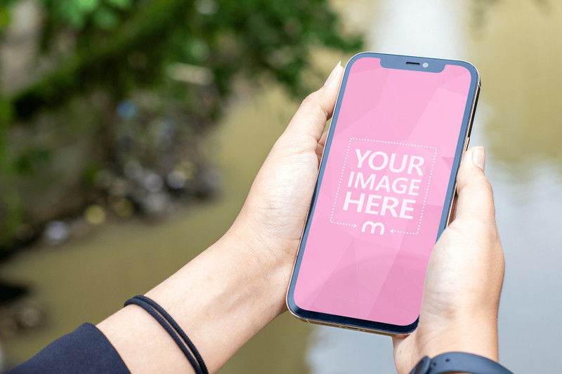 Mockup of an iPhone Featuring a Woman Hold it With Polluted River as the Background preview image