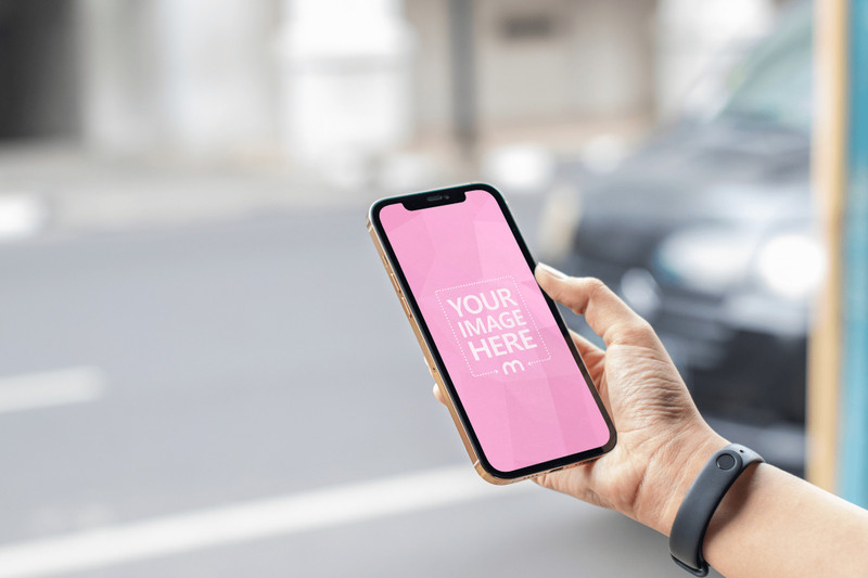 Mockup of a Gold iPhone With Black Car as the Out of Focus Background