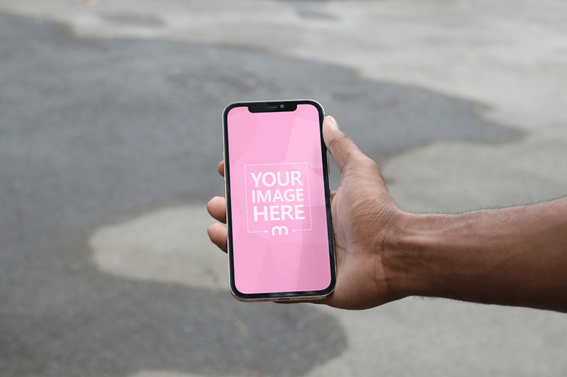 iPhone Mockup Featuring a Black Hand Holding it While Showing Wet Street