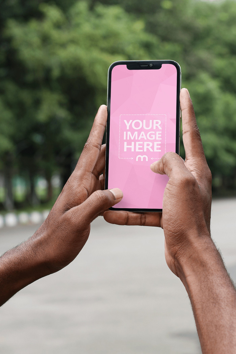 Mockup of an iPhone Held by Both Hands While Showing Park Scenery