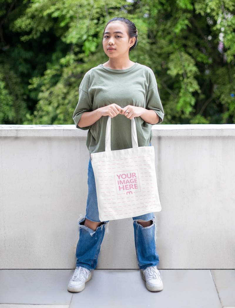 Tote Bag Mockup With a Woman Holding it Below Her Chest
