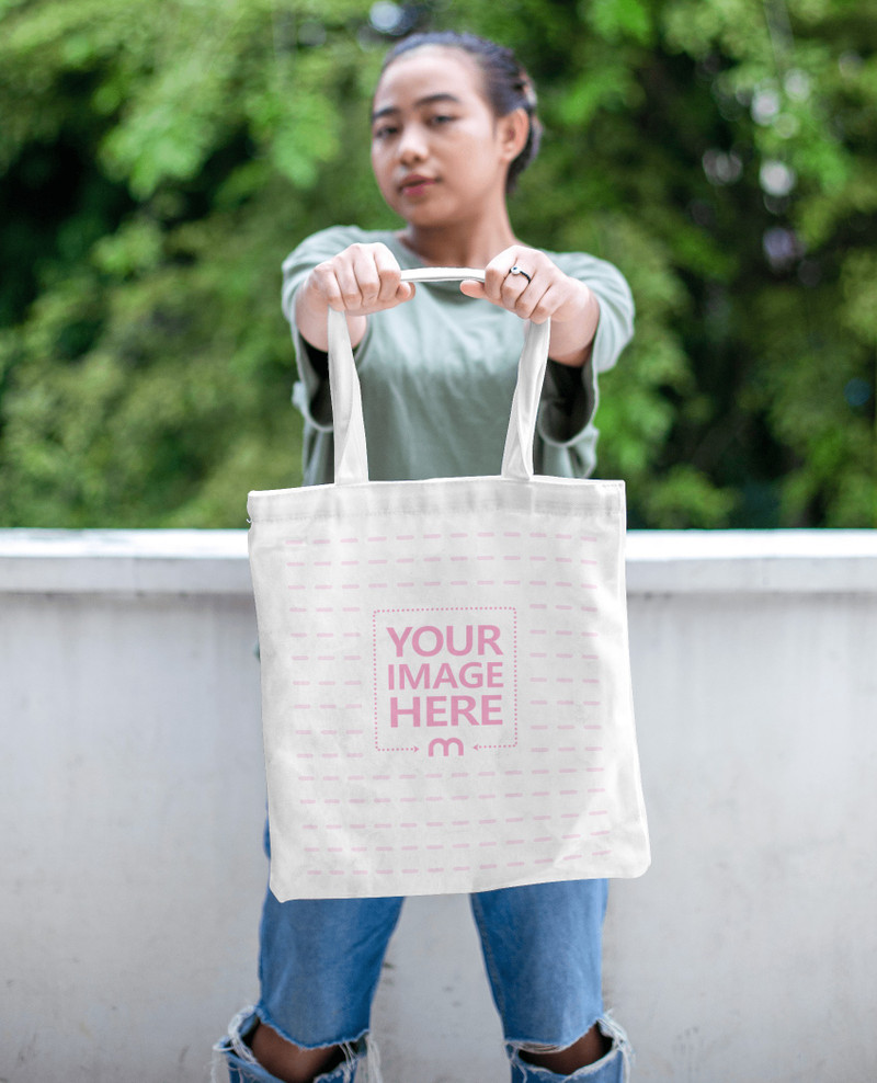 Mockup of a Tote Bag With a Woman Showing off Her Bag