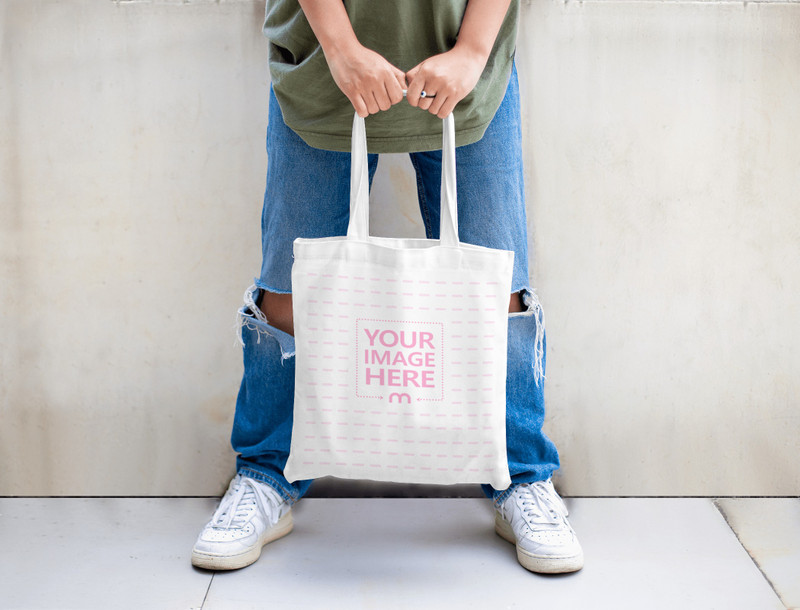 Tote Bag Mockup Featuring A Woman Showing Her Tote Bag Along With Her Ripped Jeans
