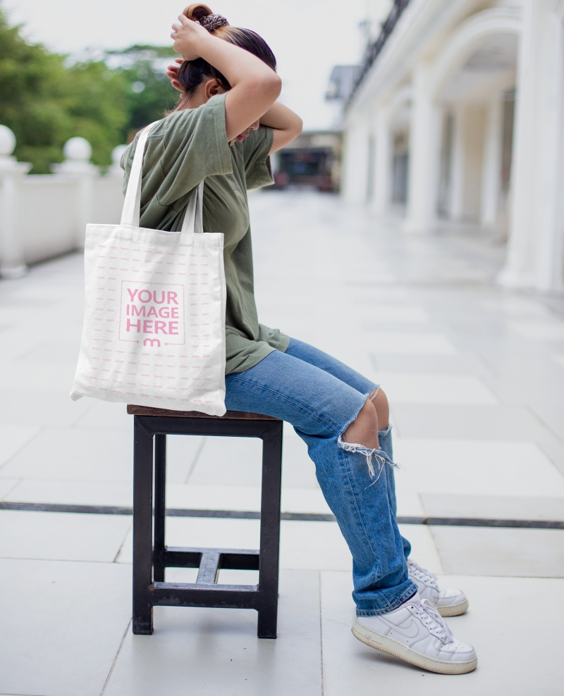 Tote Bag Mockup With A Woman Holding it on Her Shoulder While Fixing Her Hair