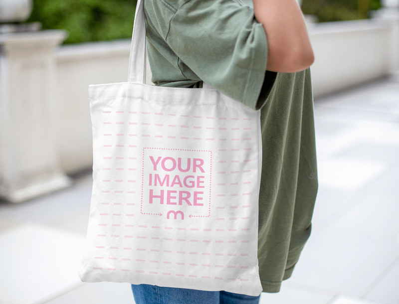 Mockup of a Tote Bag on The Shoulder of a Woman Wearing Her Green Shirt