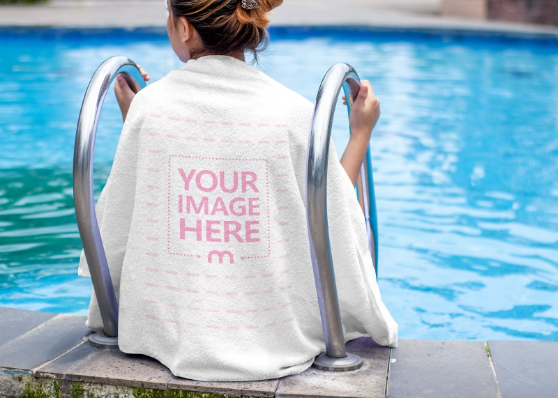 Mockup of a Towel Wrapped around a Back Side of a Sitting Woman at a Swimming Pool