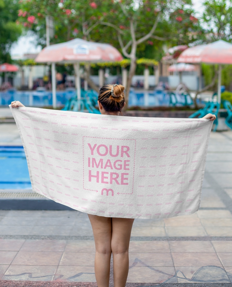 Mockup of A Towel With a Woman Spreading it Around Her Back With Pools as the Background