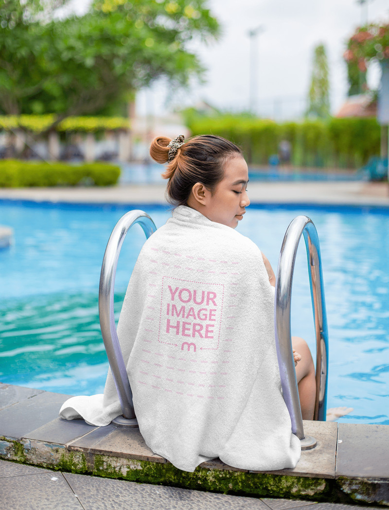 Towel Mockup Wrapped Around the Back of a Woman While She Facing Sideways at a Swimming Pool