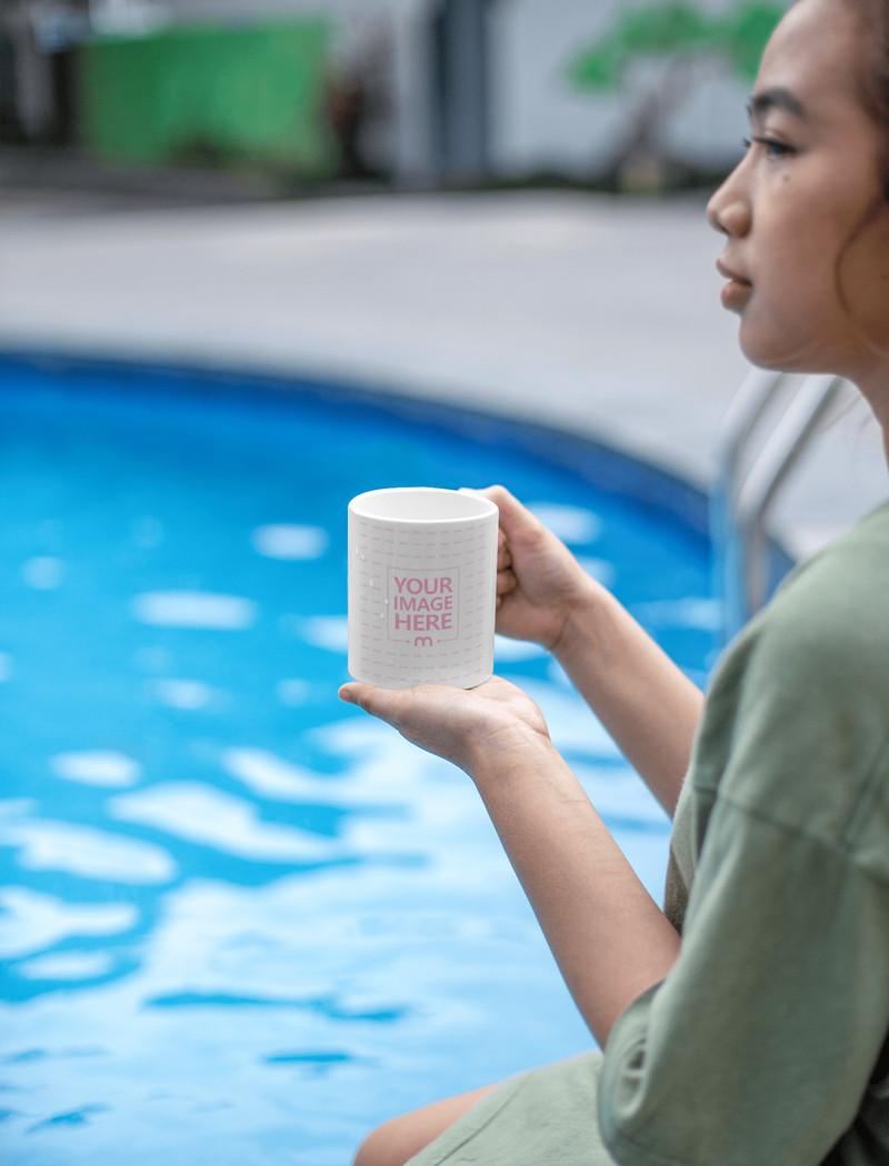 Mug Mockup Featuring a Brown Hair Woman Holding it With Her Both Hands at a Pool
