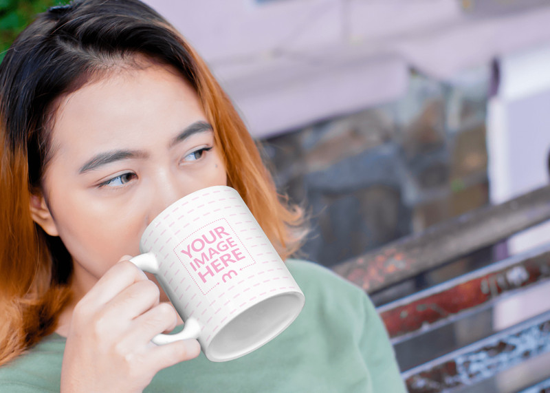 Mug Mockup Featuring A Young Woman Drinking From it While Sitting on a Bench