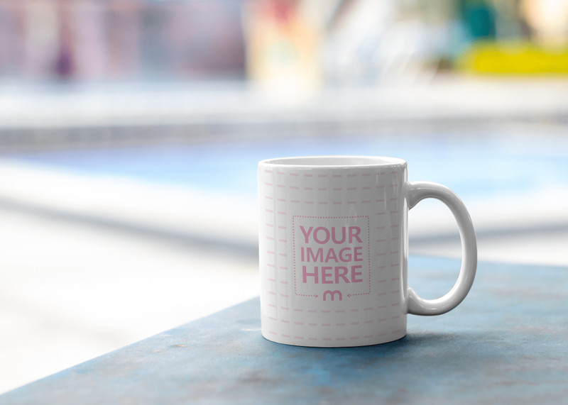 Mockup of a Mug Placed on top of a Table With a Pool as the Background