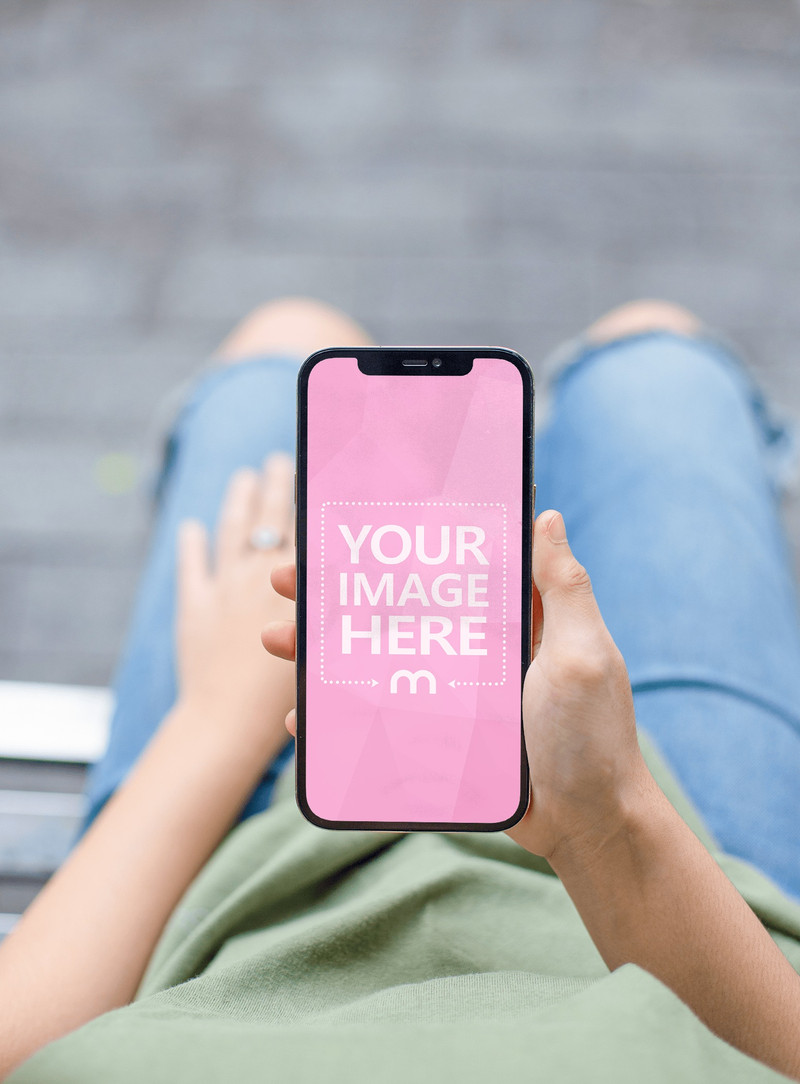 Mockup of an iPhone Featuring a Woman holding it on with her Ripped Jeans on the Scene