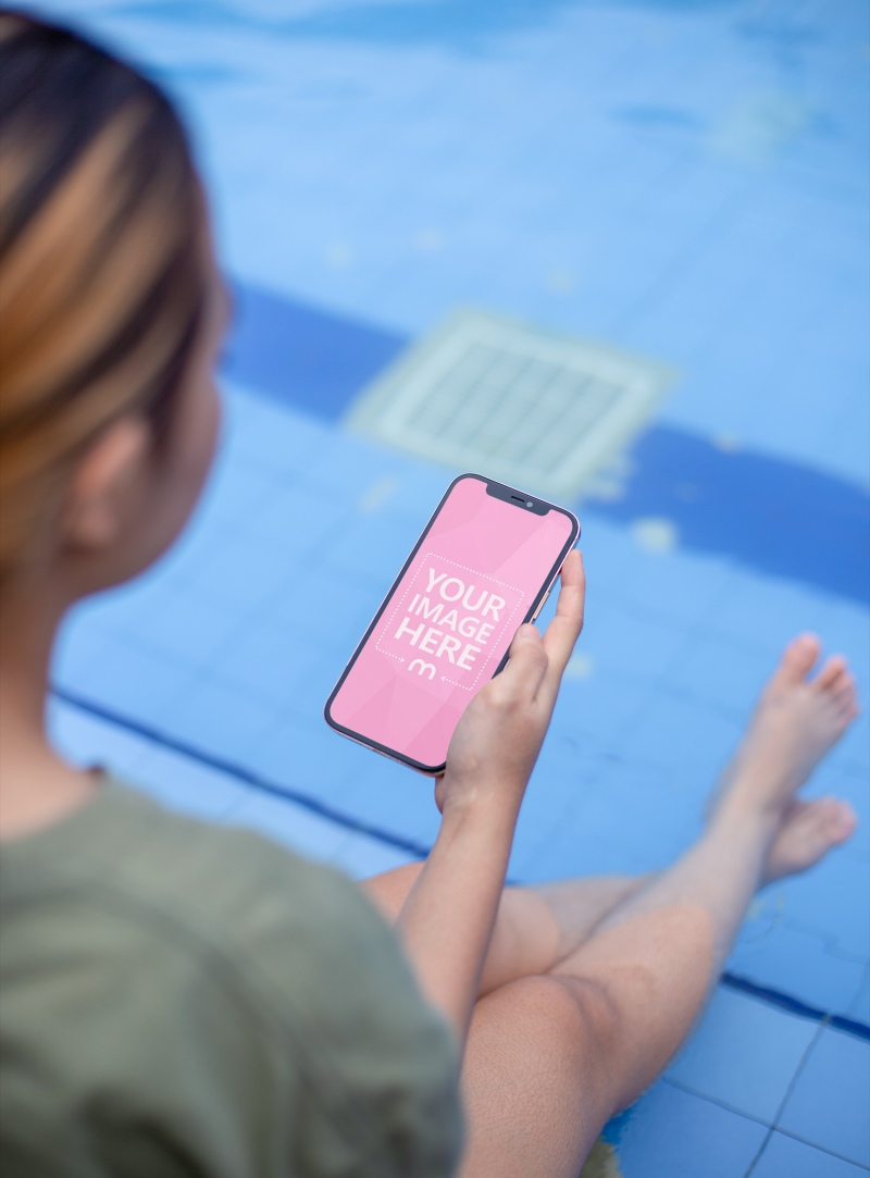 Mockup of an iPhone With a Woman Holding it on Her Right Hand While Sitting on the Poolside