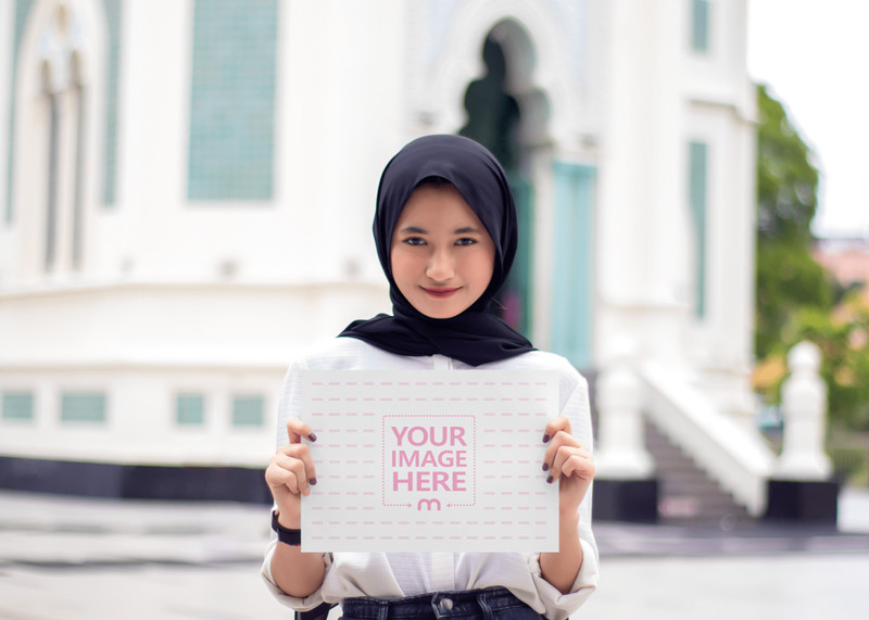 A4 Paper Mockup With a Woman Holding it in Front of a Mosque