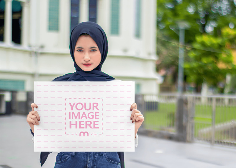 A3 Paper Mockup on a Hand of a Muslim Woman in front of a Building's Yard